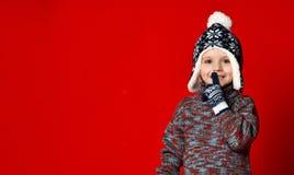 Barnpojke i stucken hatt och tröja och tumvanten som gör för att tysta gest över färgrik röd bakgrund royaltyfri fotografi