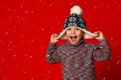 Barnpojke i stucken hatt och tröja och tumvanten som har gyckel över färgrik röd bakgrund royaltyfria foton