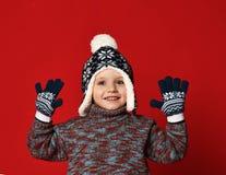 Barnpojke i stucken hatt och tröja och tumvanten som har gyckel över färgrik röd bakgrund royaltyfri fotografi