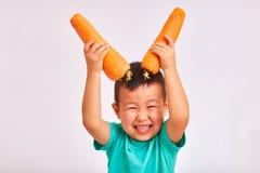 Barnpojke i turkosskjortan, enorma morötter för håll som visar horn - frukter och sund mat arkivfoton