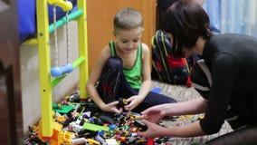 Barnpojke och hans moder som spelar med leksaker lager videofilmer