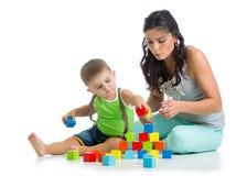 Barnpojke och moder som spelar samman med kvarterleksaker Arkivfoton