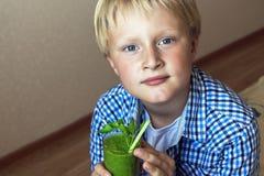 Barnpojke som dricker den gröna smoothien Royaltyfria Foton