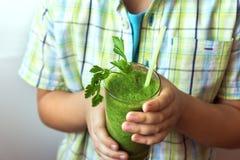 Barnpojke som dricker den gröna smoothien Fotografering för Bildbyråer