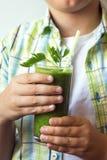 Barnpojke som dricker den gröna smoothien Royaltyfria Bilder