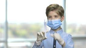 Barnpojke som förbereder injektionssprutan för injektion stock video