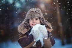 Barnpojke som har gyckel i snön Arkivbild