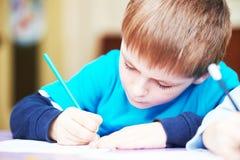 Barnpojke som studerar handstil Arkivbild