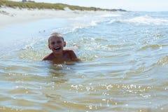 Barnpojkebad i havet arkivfoton