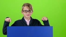Barnpojken i exponeringsglasen får övre och visar på ett bräde på en grön skärm långsam rörelse lager videofilmer