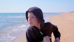 Barnpojken kör att gå på liten jogger för havssandstrand på sport utomhus lager videofilmer