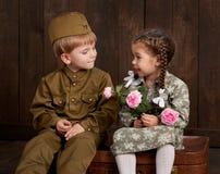 Barnpojken kläs som soldat i retro militära likformig och flicka i rosa färgklänningsammanträde på den gamla resväskan, mörk wood royaltyfri fotografi