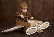 Barnpojken kläs, som soldaten i retro militära likformig reparerar ett flygplan som göras av kartongen, mörk wood bakgrund, retur Royaltyfria Bilder