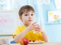 Barnpojken med ett exponeringsglas av nytt mjölkar Arkivfoton