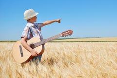 Barnpojken med gitarren är i det gula vetefältet, den ljusa solen, sommarlandskap Arkivbild