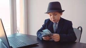 Barnpojken ser som en affärsman i hatt och dräkt i hans kontor som sitter på tabellen som räknar dollar nära bärbara datorn lager videofilmer