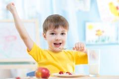 Barnpojken som äter sädesslag med jordgubbar och dricker, mjölkar Arkivbild