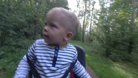 Barnpojkesammanträde på cykelstol, medan köra och se omkring arkivfilmer