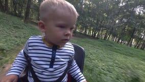 Barnpojkesammanträde på cykelstol, medan köra och se omkring lager videofilmer