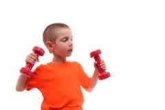 Barnpojkesport som övar isolerade lönelyfthantlar royaltyfri bild