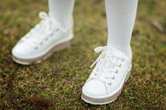 Barns ben i vita gymnastikskor som står på det utomhus- gröna gräset royaltyfri foto