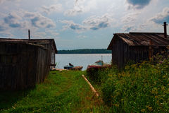 Barns and boats on lake. Lake view with old wooden barns, small pier and boats in summer Royalty Free Stock Photo