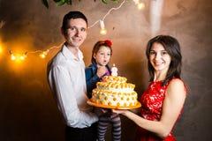 Barns för temafamiljferie födelsedag och blåsa ut stearinljus på den stora kakan ung familj av tre personer som står och Arkivfoto