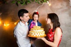 Barns för temafamiljferie födelsedag och blåsa ut stearinljus på den stora kakan ung familj av tre personer som står och rymmer 5 Royaltyfria Bilder