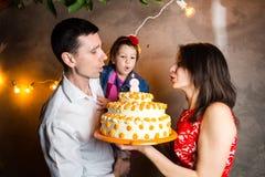 Barns för temafamiljferie födelsedag och blåsa ut stearinljus på den stora kakan ung familj av tre personer som står och rymmer 5 Royaltyfri Fotografi