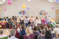 Barns ferie i dagis Barn på etapp utför framme av föräldrar bild av suddighetsunges show på etapp på skolan Arkivbilder