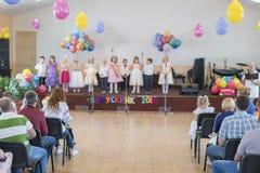 Barns ferie i dagis Barn på etapp utför framme av föräldrar bild av suddighetsunges show på etapp på skolan Royaltyfri Bild
