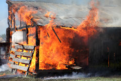 Barns on fire. Controlled burning of a few old building Royalty Free Stock Image