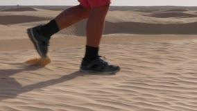 Barns fot i gymnastikskor promenerar sanden Pojken som hoppas från kullen closeup arkivfilmer