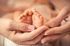 Barns fot i händerna Arkivbild