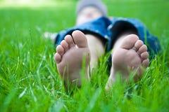 Barns fot på gräs. picknick i fjäderpark Arkivfoto