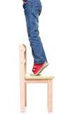Barns fot som står på den lilla stolen på tåspetsarna Arkivfoton