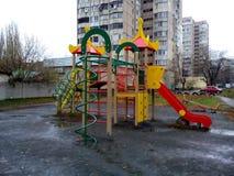 Barns glidbana i parkeraområdet av ‹för †staden på en regnig dag Arkivbilder