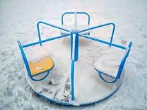Barns gunga för rotation i en cirkel på en tom bakgrund av snö arkivfoton