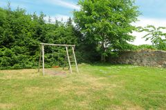 Barns gungauppsättningen i gräsplan parkerar Eco trädgård arkivfoto
