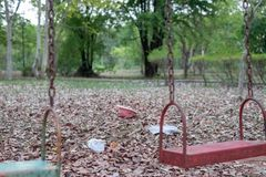 Barns gungor hänger tomt ett overksamt på en lekplats på en tråkig mulen dag Borttappad barndag royaltyfri fotografi