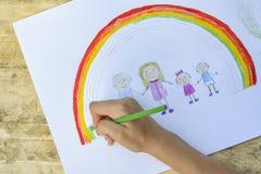 Barns händer målar en teckning med en borste och målarfärger överkant VI royaltyfria bilder