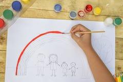 Barns händer målar en teckning med en borste och målarfärger överkant VI fotografering för bildbyråer