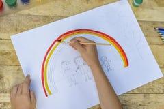 Barns händer målar en teckning med en borste och målarfärger överkant VI royaltyfri foto