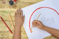 Barns händer målar en teckning med en borste och målarfärger överkant VI royaltyfri fotografi