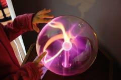 Barns händer på en plasmaboll royaltyfria bilder