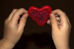 Barns händer rymmer plasticinehjärta arkivbild
