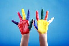 Barns händer som målas med mångfärgade fingermålarfärger royaltyfria bilder