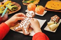 Barns händer som rymmer kakor i form av monster Arkivfoto