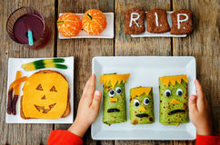 Barns händer som rymmer plattan med lunch i form av monster Royaltyfri Fotografi