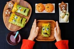 Barns händer som rymmer plattan med lunch i form av monster Royaltyfri Foto